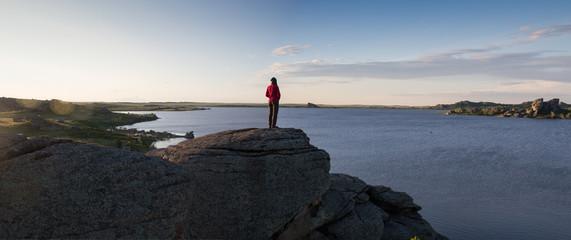 Young woman sitting on rock and enjoying beautiful view