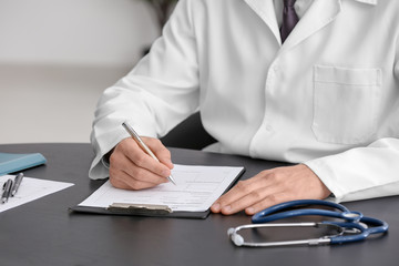 Doctor filling in insurance form at table