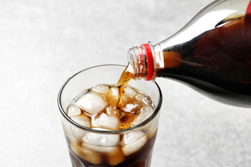 Pouring cola from bottle into glass with ice on light background, closeup