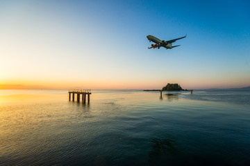 Modern civilian airplane landing at early morning. Flew above airport approach landing light on the Ionian sea at Corfu international airport, Greece.