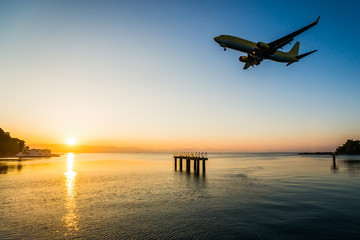 Modern civilian airplane landing at early morning in first beam of sunlight. Flew above airport approach landing light on the Ionian sea at Corfu international airport, Greece.