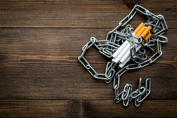 Quit smoking. Cigarettes in chains on dark wooden background top view copy space