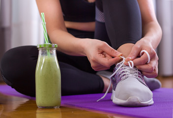 Sporty woman tying shoelaces on floor