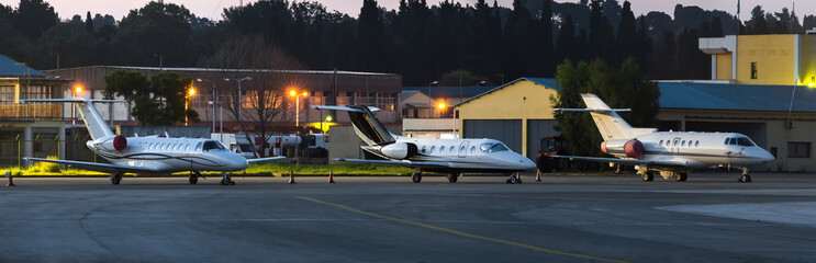 Scenic night view of private business jets standing on parking place at Corfu Ioannis Kapodistrias international airport.