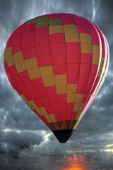 A multi colored hot air balloon fly in the blue sky