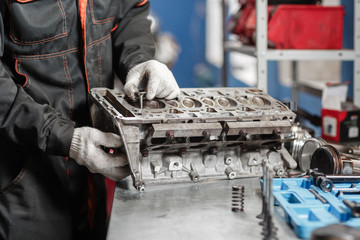 the mechanic installs a new valve. Disassemble engine block vehicle. Motor capital repair. Sixteen valves and four cylinder. Car service concept.