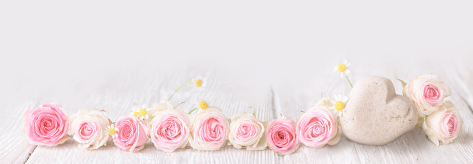 Pink roses and stone heart on rustic wooden background