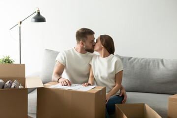 Happy couple kissing on sofa moving in own house, young man and woman sitting on couch with cardboard boxes and blueprint plan, first time homeowners starting living together settle in new apartment
