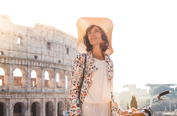 Beautiful young woman in colorful fashion dress alone in front of colosseum in Rome at sunset. Attractive girl tourist taking off elegant straw hat.