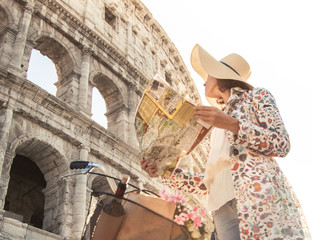 Beautiful young woman in colorful fashion long dress with bike reading map in front of colosseum in Rome at sunset. Happy attractive tourist girl with straw hat looking for directions. Ground shot.