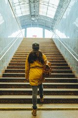 woman climb stairs with bags at railway station