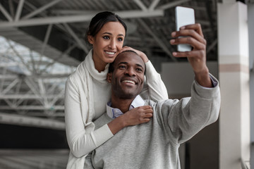 Say cheese. Portrait of joyful enamored young couple is standing at airport hall and making selfie using smartphone. Woman is hugging man from behind with smile