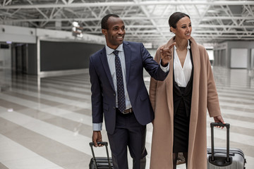 This is amazing. Delighted elegant business partners are going together with their suitcases. Man is pointing finger and expressing gladness while looking aside with smile. Copy space