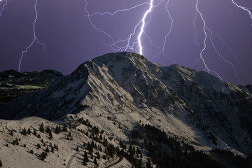 lightning falling over the snow-capped mountains