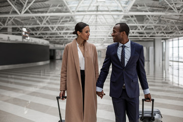 Feeling happiness. Pleasant romantic young couple are looking at each other with love while holding hands and carrying suitcases while going along airport lounge