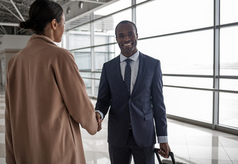 Portrait of happy delighted young african businessman is exchanging greetings with lady. They are standing against big window while male is looking at camera with joy. Back view of female