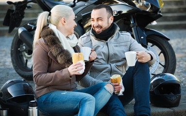 Cheerful young smiling couple having picnic with coffee