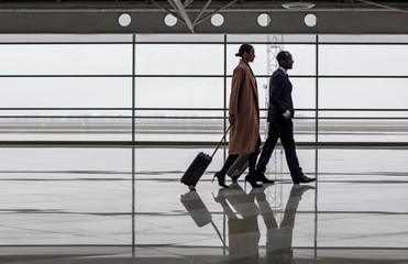 Joint travel. Full length profile of successful business partners are going along airport with suitcases. Glass wall in background and copy space in left side