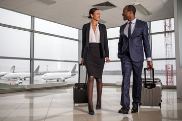 Joint trip. Full length portrait of confident successful business partners are going along airport with suitcases. Lady looking at man with smile. Aircrafts in background and copy space in left side