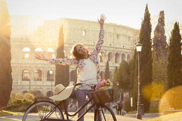 Beautiful young woman in colorful fashion long dress with bike spreading arms and smiling to camera in front of colosseum in Rome at sunset on a road with trees. Happy attractive girl tourist in colle