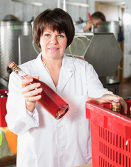 Careful female worker packaging wine bottles