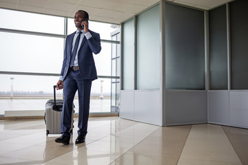 Phone communication. Full length portrait of elegant cheerful man in suit is standing at airport lounge with suitcase. He is looking aside with smile while having pleasant conversation on mobile. Copy