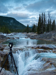 Camera on a tripod setup in front of a waterfall