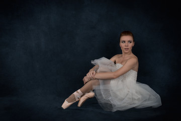 the ballerina in pointes and a white dress sits
