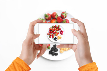Girl taking picture of different kind of berries on plate