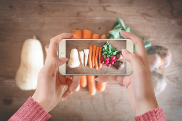 Girl taking picture of vegetables on wooden table with her smartphone for her blog