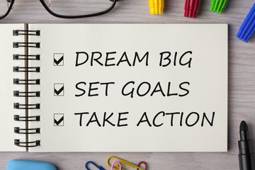 Dream Big, Set Goal, Take Action written in notebook