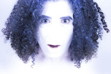 A noseless surprised man like alien with white skin and blue curly hair