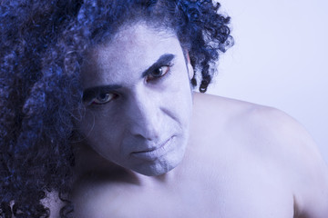 Blue Curly Hair and White Skin Man leering at camera