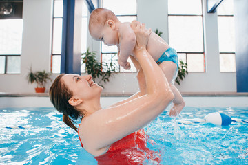 White Caucasian mother traning her newborn baby to float in swimming pool. Happy mom parent holding her child up in water. Healthy active lifestyle. Family indoor activity, early development concept