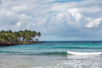 sea surf in the Dominican Republic. Sea, shore with palm trees and sky with storm clouds