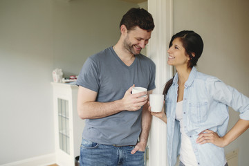 Young couple smiling holding coffees cups.