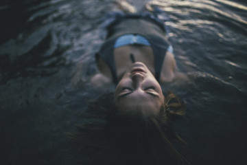 Woman floating on back in water with eyes closed.