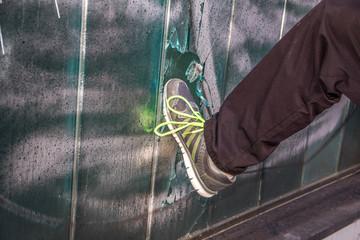 Mann mit Sneakers tritt Scheibe ein