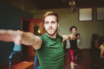Man in yoga class with arms outstretched.