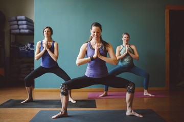 Three women in prayer position in yoga class.