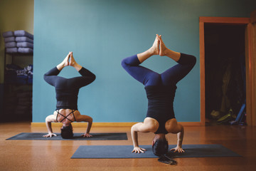 Two women doing headstands in yoga class with feet together.