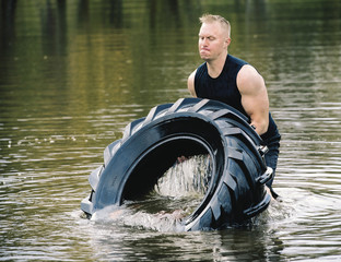 Man lifting tyre in water.