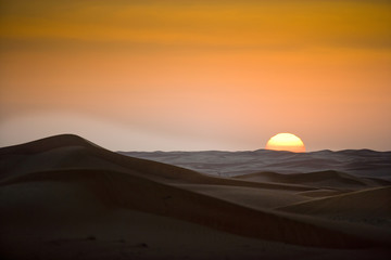Sand dunes in desert sunset.