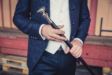Man holding silver topped cane.
