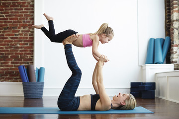 Mother and daughter doing yoga together, daughter balancing on mother's feet