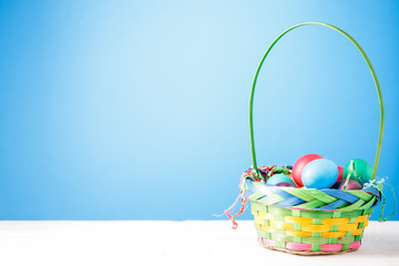 Photo of basket with colorful eggs on empty blue background.