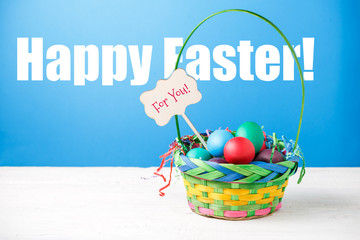 Photo of basket with colorful eggs with wish for happy Easter