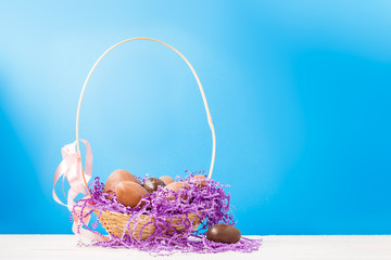 Image of chicken, chocolate eggs, purple decorative paper in basket