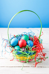 Picture of basket with colorful eggs on empty blue background
