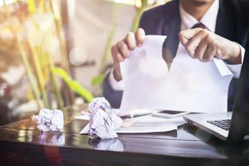 Businessman strain on earnings.shredded paper
